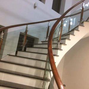 cầu thang kính cong tay vịn gỗ